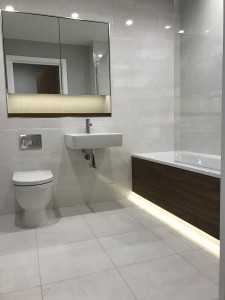 New modern bathroom at Cornwall works with light grey tiles and white and dark wood suite
