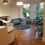 Waiting area and reception with feature light and parquet flooring at The Dental Centre, Tulse Hill