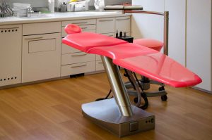 Red dental chair in modern clinic