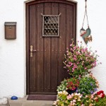 Rustic wooden front door with begonias and assorted flowers