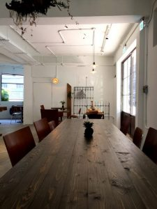 Long wooden table surrounded by chairs in a loft style space