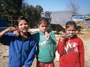 Three Nepalese girls brushing their teeth with toothbrushes supplied by Dentaid