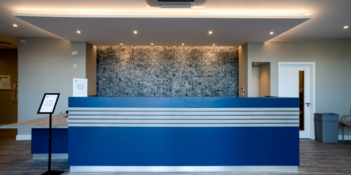 Bespoke reception desk at Angle House clinic in Harrow. The desk is blue with LED lighting underneath.