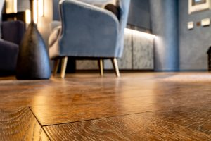 Close up of hardwood floor with grey armchair
