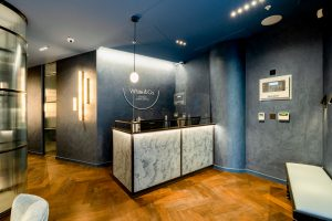 White marbled reception desk with hardwood floor and grey walls